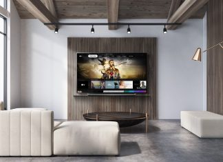 A view of an LG TV hanging on the wall of a wide modern living room as it displays the Apple TV app.