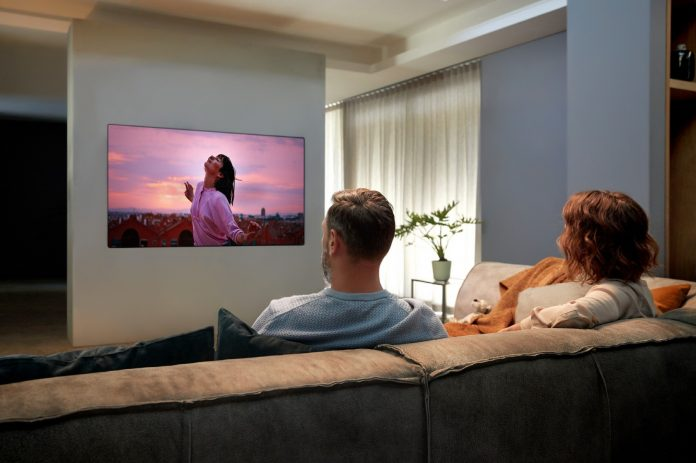 A man and a woman enjoying the state-of-the-art picture quality that comes with LG OLED TV GX on their cozy living room sofa.